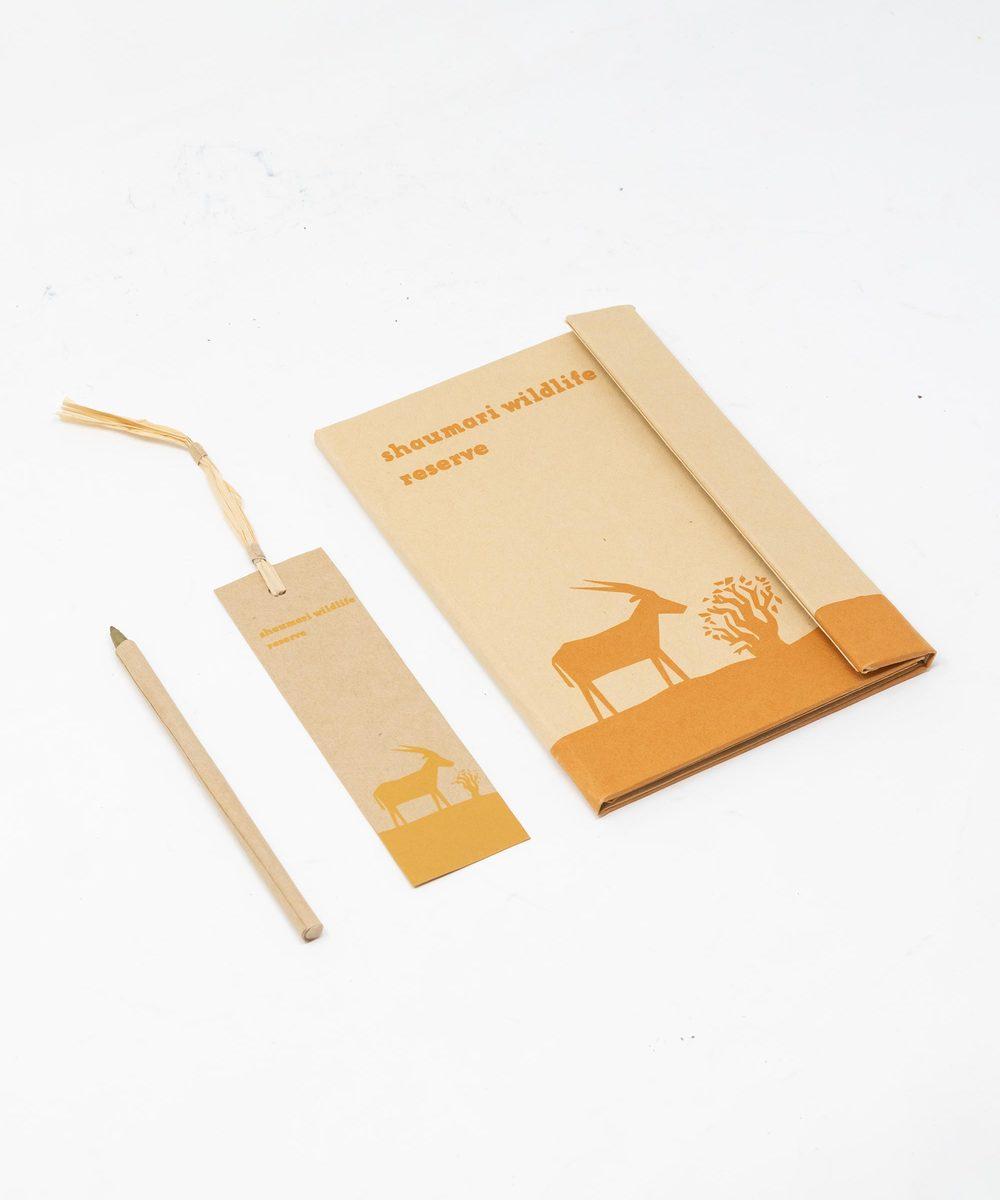 دفتر ملاحظات مع قلم وفاصلة كتب باللون البرتقالي.