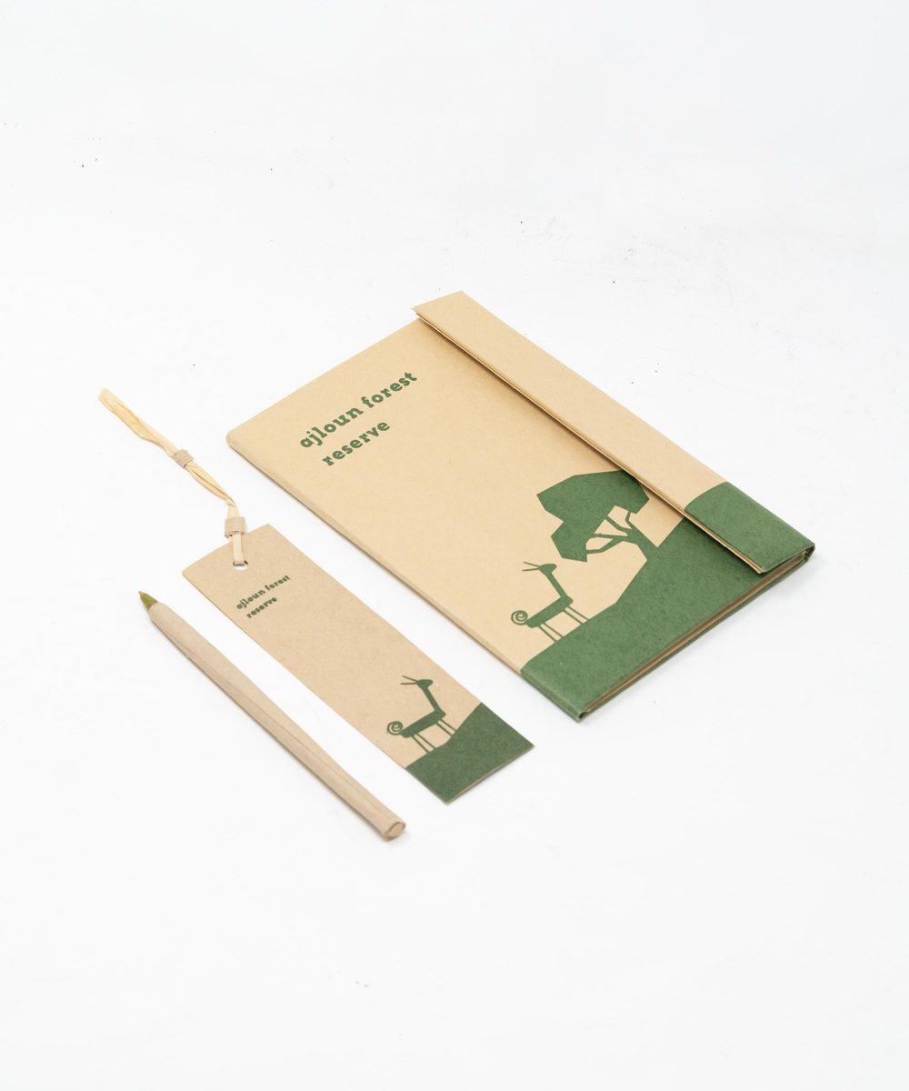 دفتر ملاحظات مع قلم وفاصلة كتب باللون الأخضر الداكن.