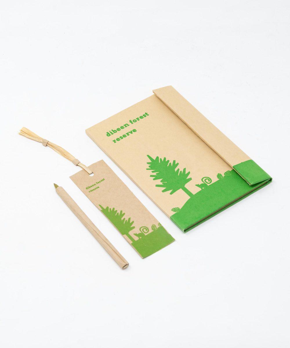 دفتر ملاحظات مع قلم وفاصلة كتب باللون الأخضر الفاتح.