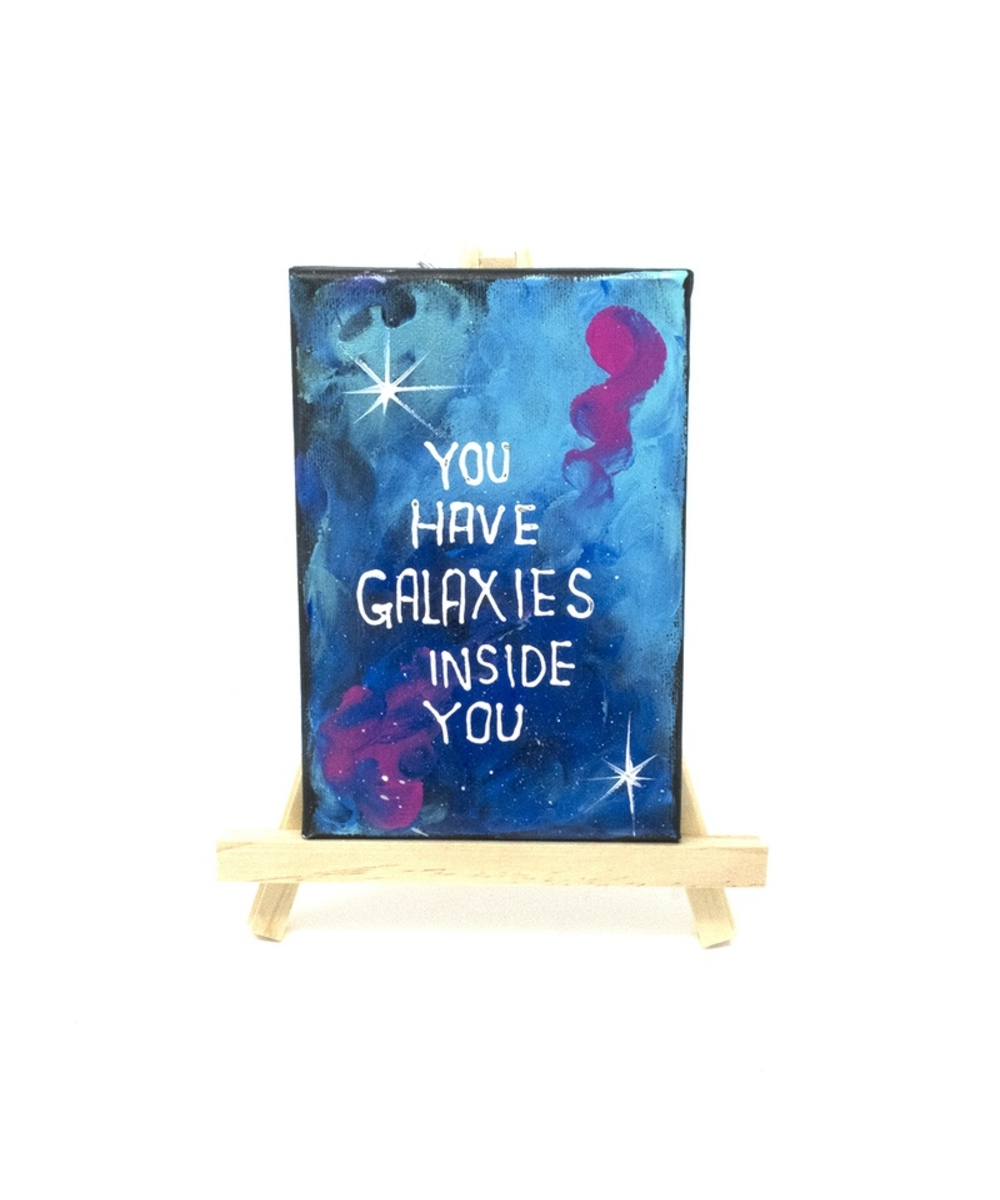 A small painting with the Phrase &You have galaxies inside you&