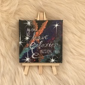A small painting with the Phrase You have galaxies inside you